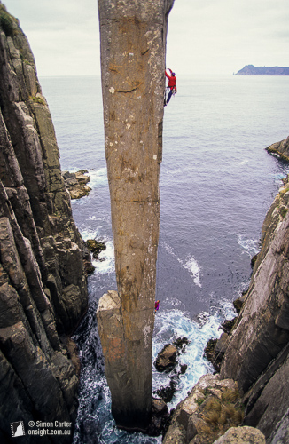 Steve Monks aid climbing The Totem Pole with Simon Mentz belaying, in 1995. This was then was the only route up the Totem Pole – until the pair returned a few days later and established the Free Route. Cape Hauy, Tasmania, Australia.