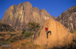 Fred Moix boldering on a V6 with the Tsaranoro massif in the background, Tsaranoro, Madagascar.