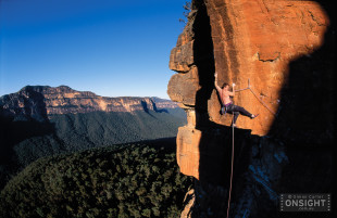Mike Law attempts to free climb pitch four of his gripping new 190 metre epic, Red Edge, near Perrys Lookdown in the Grose Valley, Blue Mountains, NSW, Australia. Pitches are 23, 24, 22, 26 and 24. Mount Banks is in the background. Red: 070 001 24.