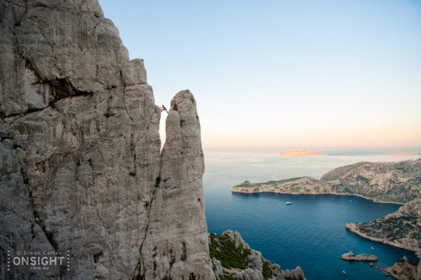Sunrise finds Nadine Rousselot and Mathieu Geoffray an hours hike in and two pitches up Arête de Marseille (5c). It is a five pitch Calanque's classic first climbed in 1927, on La Grande Candelle, overlooking the Mediterranean, France.