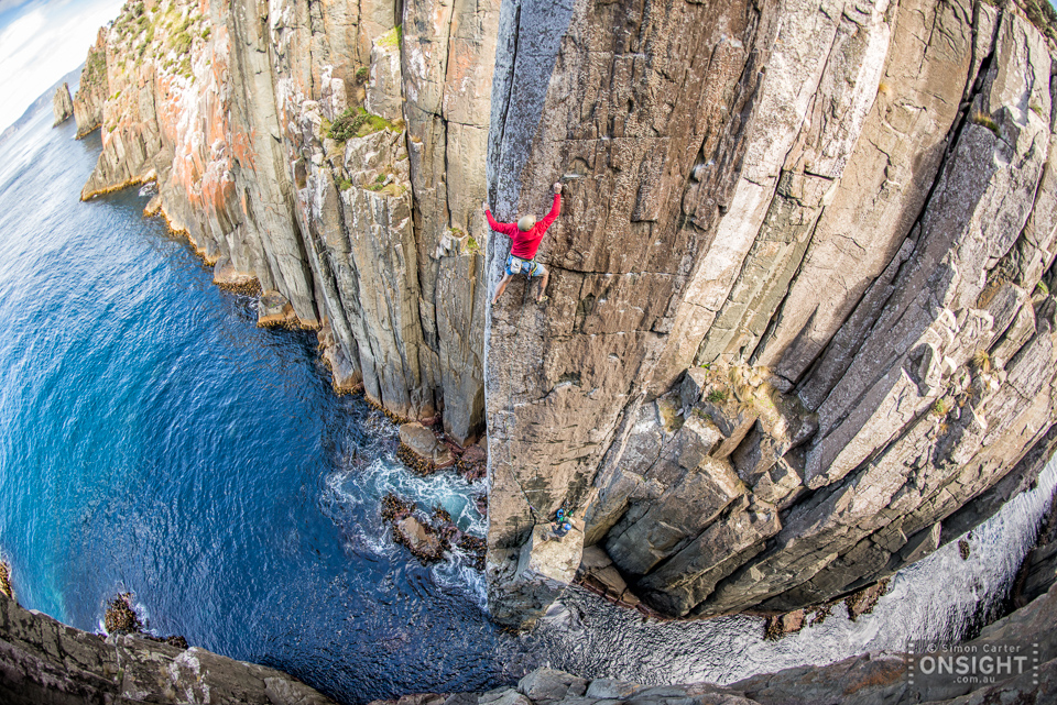 Chris Coppard on The Sorcerer (27) with Garry Phillips belaying, a new independant route that they established on the Totem Pole in 2015 -- some 20 years after the first free ascent of the 65m high pillar. Cape Hauy, Tasman Peninsular, Tasmania, Australia.